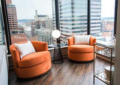 a room with two orange chairs and a city view