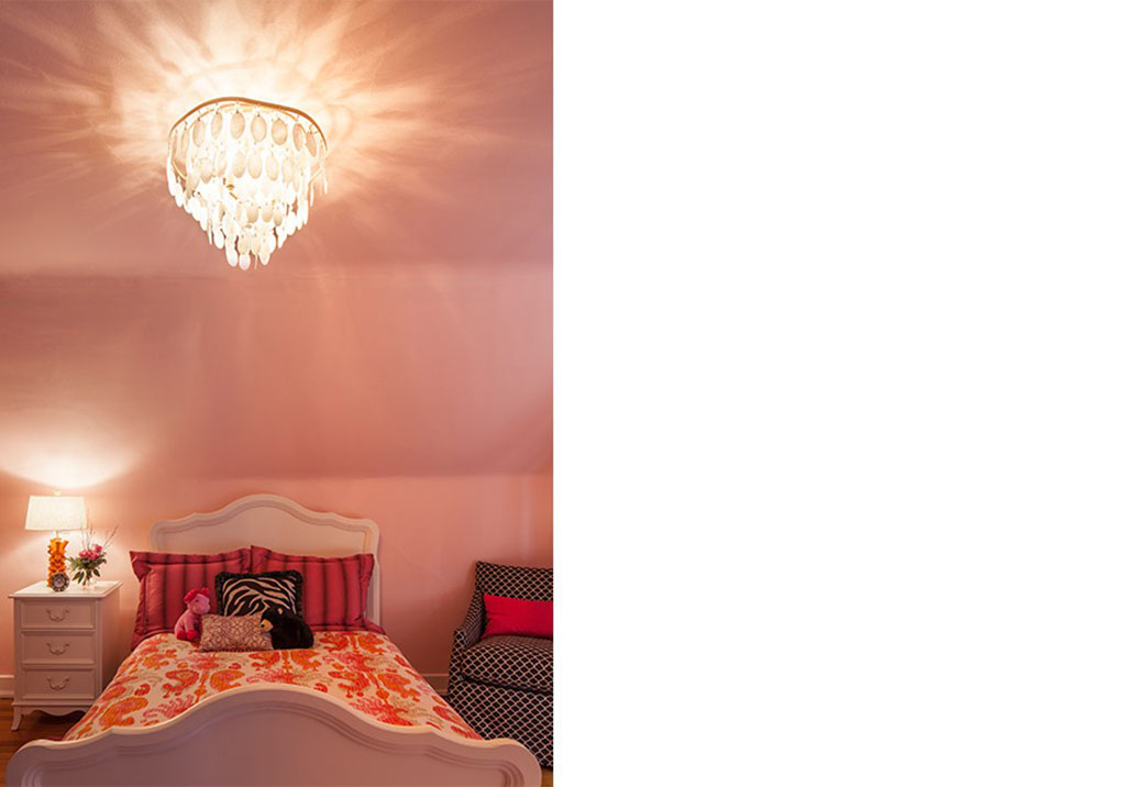 a bedroom with pink walls and a glass chandelier