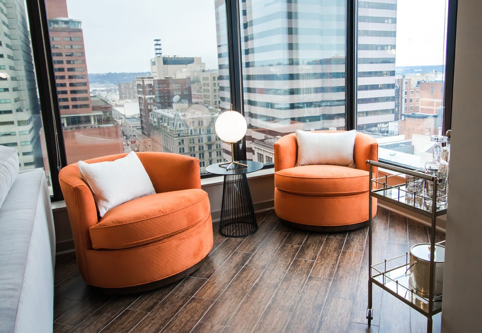 room with two orange chairs and a view of skyscrapers