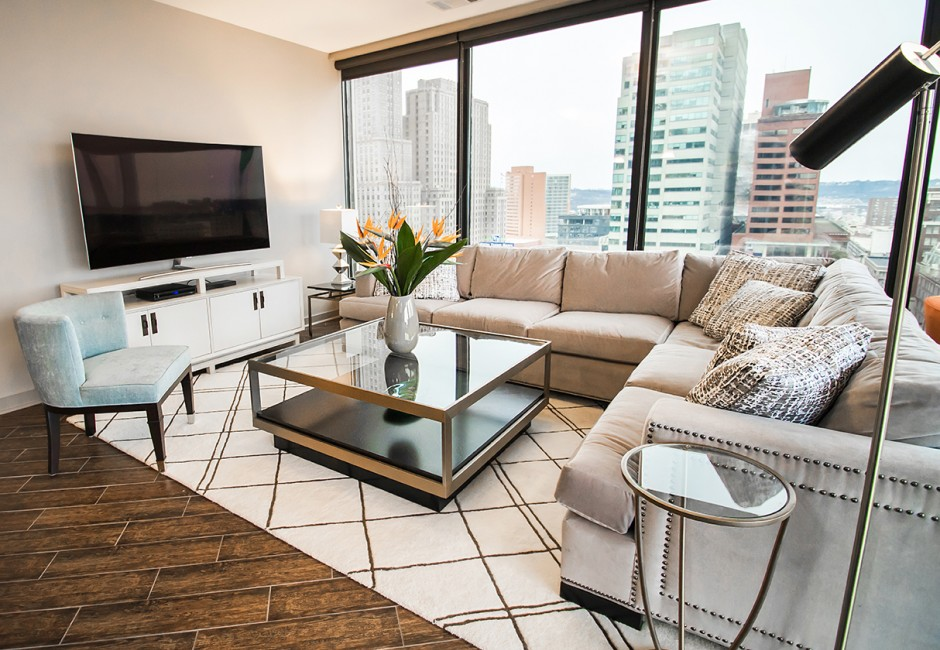 living room with a couch, tv, and a view of skyscrapers
